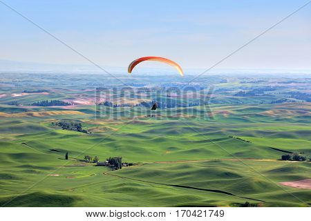 Para glider up in sky above rolling hills