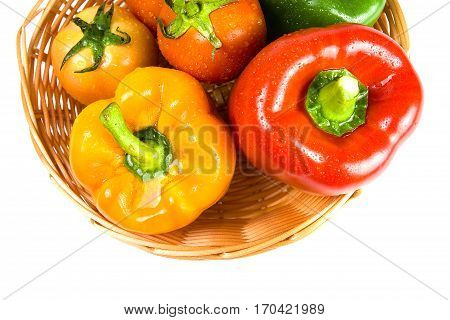 Sweet peppers tomato and carrot in basket on white background