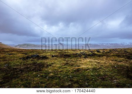 The wild and vast landscape of south Iceland under a overcast dark sky.