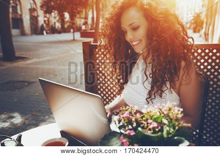 Smiling beautiful white caucasian freelancer girl with curly hair is sitting in street cafe in front of wooden fence and working on her modern laptop on sunny day