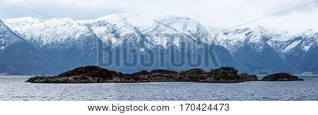 Panoramic view over an island in a norwegian fjord with a mountain range in the background