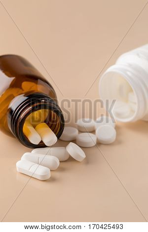 Glass and plastic pills bottle on beige background