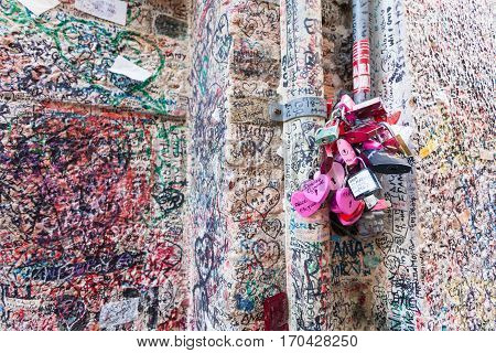 VERONA ITALY- September 08 2016: The wall full of messages on different foreign languages from lovers and some pink locks in Juliet house in Verona.