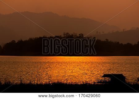 Sihouette houseboat in the river with mountain view on the sunset Sangkhlaburi Kanchanaburi Thailand