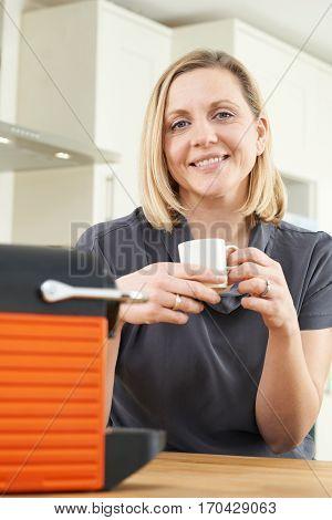 Woman Using Coffee Capsule Machine In Kitchen