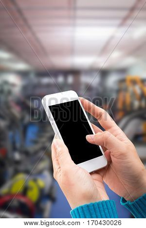 Woman hand holding and using mobilecell phonesmart phone with isolated screen with blurred of department store the for background.