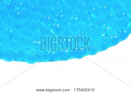 Pile of blue soil water beads isolated over the white background, close-up crop fragment