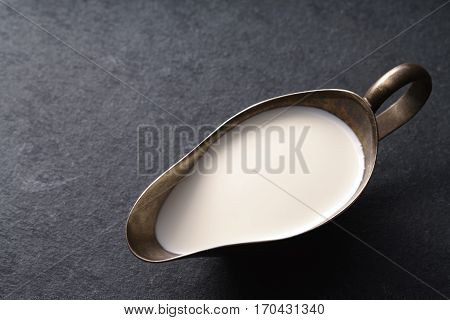 Cream in vintage gravy boat on a gray slate on the right horizontal