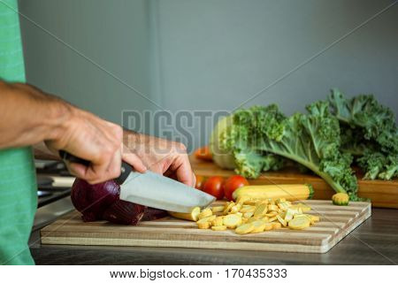 Mid-section of man chopping vegetables in kitchen
