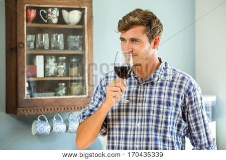 Young man smelling a glass of red wine in kitchen