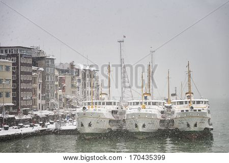 ISTANBUL,TURKEY, FEBRUARY 8, 2017: Sehir Hatlari passenger ferries docked at Karakoy Pier, sea transportation is cancelled, Istanbul under heavy snow.