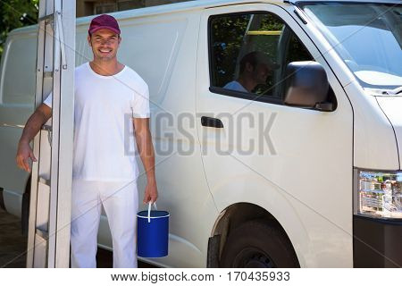 Portrait of painter holding stepladder and bucket standing near his van