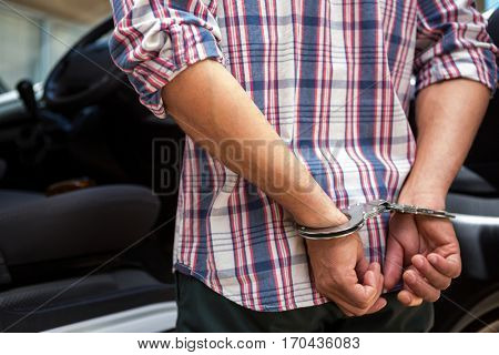 Rear view of man handcuffed behind his back