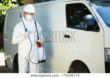 Portrait of pest control man standing next to a van on a street