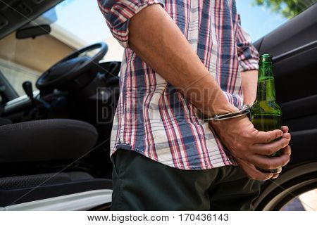 Mid section of man handcuffed behind his back for drinking and driving