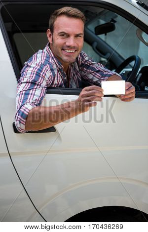Portrait of young man showing his drivers license