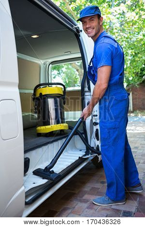 Portrait of happy janitor cleaning the car with vacuum cleaner