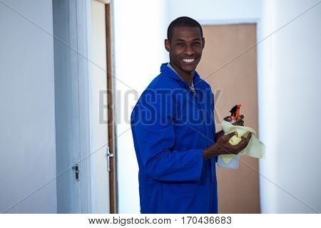 Happy handyman holding spraying insecticide and napkin at home
