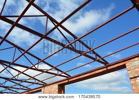 Steel roof trusses details. Steel roof trusses sitting on concrete pole view from inside home factory.