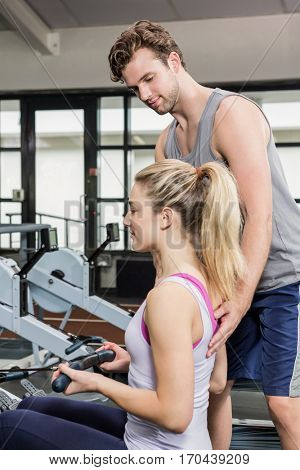 Trainer assisting a woman on rowing machine at gym
