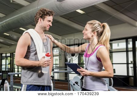 Man interacting with his trainer after a workout at gym