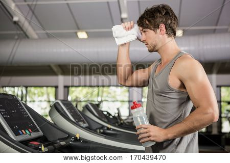 Tiered man standing on treadmill with water bottle at gym