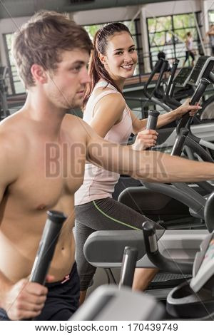 Happy man and woman exercising on the elliptical machine at gym