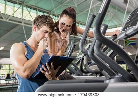 Trainer and a woman looking at the clipboard at gym