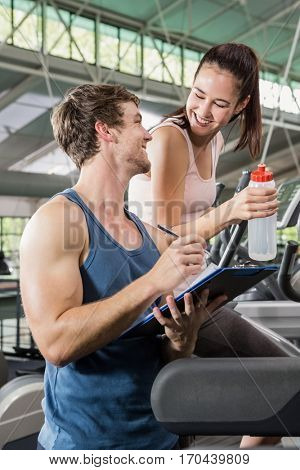 Trainer writing on a clipboard while woman exercising on a elliptical machine at gym
