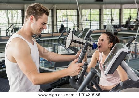 Trainer yelling through a megaphone while man exercising on elliptical machine at gym