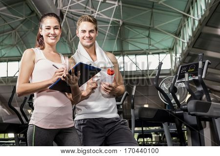 Portrait of man standing with trainer at gym