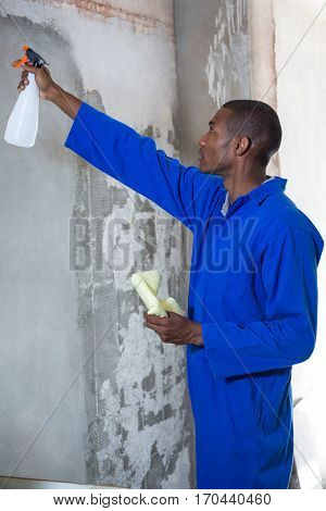 Man doing pest control on a wall in a new house