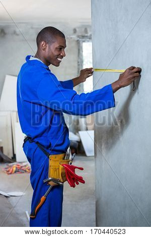 Happy handyman measuring a wall in a new house
