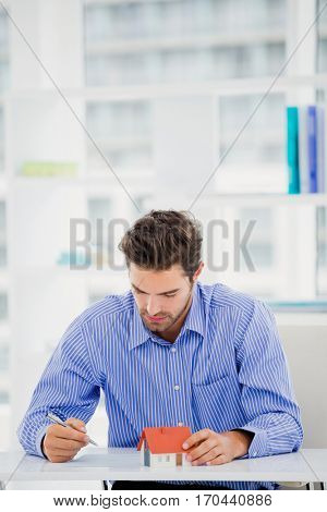 Businessman holding a model house and writing on paper in office