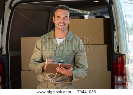 Happy delivery man writing on a clipboard next to a delivery van