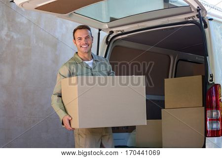 Happy delivery man carrying a cardboard box for delivery