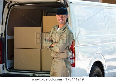 Portrait of a happy delivery man standing next to delivery van