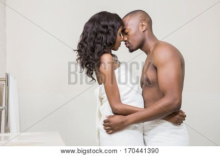 Young couple in towel standing face to face in the bathroom