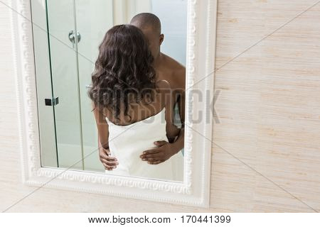 Reflection of young couple in towel standing face to face in the bathroom