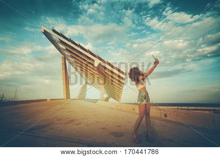 Woman is shooting selfie on touch pad in front of huge futuristic solar panel. Female wanderer is making photo of herself with digital tablet camera in front of modern photovoltaic power station