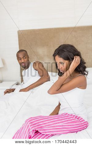 Young woman sitting on bed after an argument in the bedroom