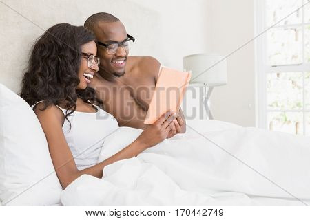 Young couple in spectacles reading book in the bedroom