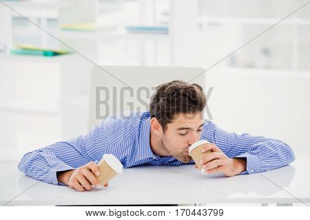 Businessman having coffee from disposable cup in office