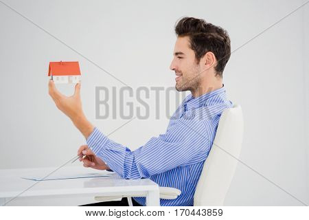 Businessman holding a model house in office