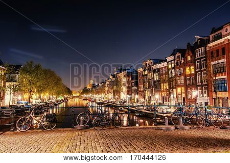 Bicycles Parked Along a Bridge Over the Canals of Amsterdam, Netherlands. Night illumination of buildings and boats near the water in the canal.