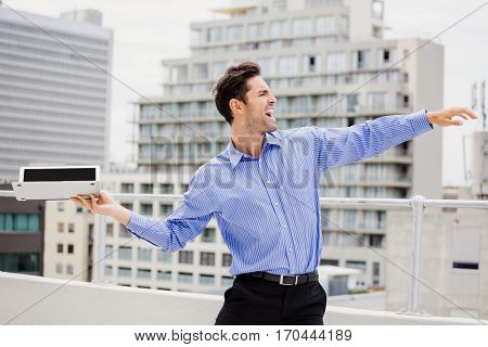 Frustrated businessman throwing laptop on office terrace