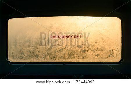 Emergency exit sign on a misty bus rear window