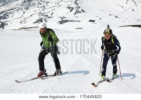 AVACHA VOLCANO KAMCHATKA PENINSULA RUSSIA - APRIL 21 2012: Open Cup of Russia on Ski-Mountaineering on Kamchatka - man and woman ski mountaineer climb on mountain on skis strapped to climbing skins
