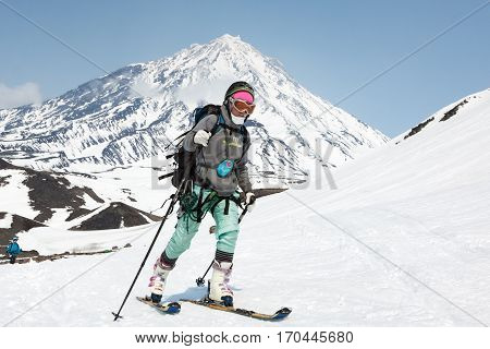 AVACHA VOLCANO KAMCHATKA PENINSULA RUSSIA - APRIL 21 2012: Open Cup of Russia on Ski-Mountaineering on Kamchatka - young woman ski mountaineer climb on mountain on background Koryak Volcano.