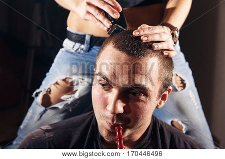 Young punk girl cuts her boyfriend using clippers.